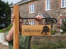 Oak Sign on wrought Iron scroll bracket - https://www.sign-maker.co.uk/made-to-measure-oak-signs-5217-p.asp
