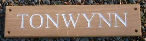 Oak sign with white lettering. http://www.sign-maker.net/wooden/oak-carved-signs.html