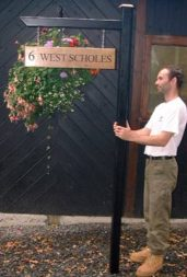 Painted wooden post and arm with oak house sign